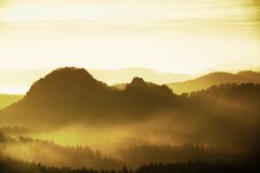 Sunrise in a beautiful mountain of Czech-Saxony Switzerland. Sharp hills increased from foggy background, the fog is orange due to Stock Images
