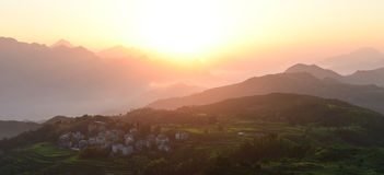 Sunrise at beautiful rice terrace fields in Mingao. Sunrise at ethnic village among highlands and mountains of southeastern China. Fields of rice terraces stock image