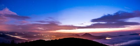 Sunrise beginning with stars above. And cars with people travelling from villages to work royalty free stock images