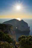 Sunrise behind the cliff with the hole. Sardinia Stock Photos
