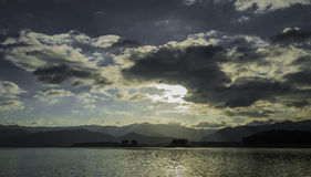 Sunrise behind the cloud in the dam Stock Image