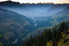 Sunset Across The Peaks at Glacier National Park. Sunrise behind the Montana Mountains with beautiful snaking river in deep valley, Glacier National Park Stock Images