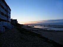 Sunrise behind oceanside buildings on beach during low tide shoreline Stock Image