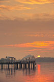 Sunrise behind a pier Stock Photo