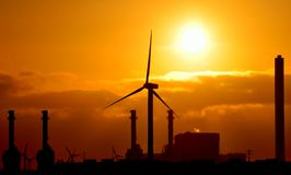 Sunrise behind power station and wind turbine Royalty Free Stock Photo