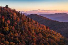 Sunrise on the Blue Ridge Parkway in Autumn illuminating colorful trees on the hillside. stock photography