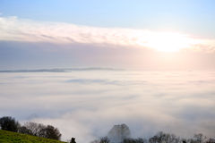 Sunrise and blue sky over fog covered landscape Royalty Free Stock Photography