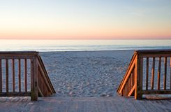 Sunrise on the Boardwalk. The first morning light from the sun reflects off the Atlantic Ocean, the sandy beach, and the steps to the beach here at the end of Stock Photography