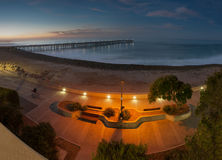 Sunrise and boardwalk lights illuminate the path. Lit walking path with Ventura pier in background Stock Images
