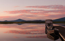 Sunrise at boat dock. Pink clouds of sunrise reflected in the still Klamath Lake water with mountains in the distance and a dock with two boats in the foreground Stock Image