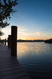 Sunrise at boat dock with boat pilings Stock Images