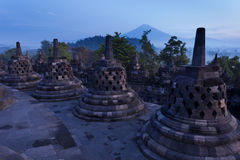 Sunrise at Borobudur temple with the bell stupas and volcano Stock Photo