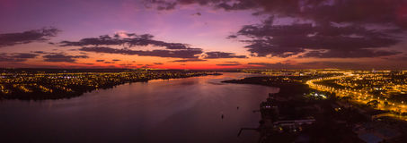 Sunrise in Brasilia. Big panoramnic sunrise in Brasilia with beautiful orange and purple colors showing city lights and a lake Royalty Free Stock Images