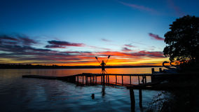 Sunrise in Brasilia. Sunrise showing a lake and wooden bridge with beautiful colors and a rowing with crossing oars Royalty Free Stock Photography
