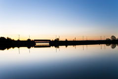 Sunrise Bridge. Mirrored View of Bridge in Glassy Lake during Sunrise Royalty Free Stock Image