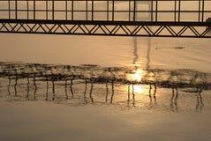 Sunrise, bridge and waves Royalty Free Stock Images