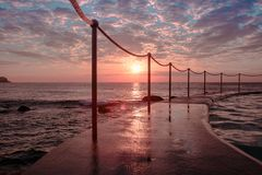 Sunrise at Bronte Beach Pool, New South Wales, Australia. Waves on the rocks stock photography