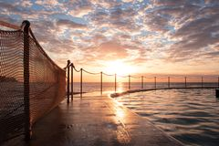 Sunrise at Bronte Beach Pool, New South Wales, Australia. Waves on the rocks stock photos