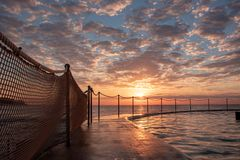 Sunrise at Bronte Beach Pool, New South Wales, Australia. Waves on the rocks royalty free stock photo
