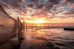 Sunrise at Bronte Beach Pool, New South Wales, Australia. Waves on the rocks royalty free stock image