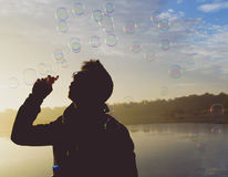 Sunrise with bubbles. Colourful morning scenery captured while sun is rising, with a man blowing soap bubbles into the air Royalty Free Stock Images