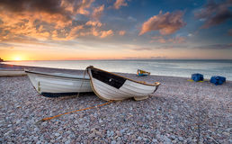 Sunrise at Budleigh Salterton. Sunrise over boats on the beach at Budleigh Salterton in Devon Royalty Free Stock Photos