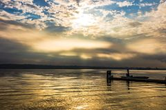 Sunrise burning off heavy clouds with pier stock photos