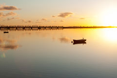 Sunrise and calmness. Over Tauranga Harbour. Water ripples bird on boat and historic rail bridge on horizon Stock Photo