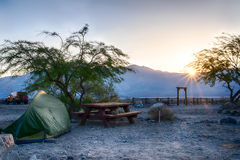 Sunrise at a campsite. In a desert at the foot of a mountain range Stock Image