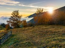Sunrise in carpathian rural area. Fence and trees along the hill. cloud inversion in the distant valley royalty free stock photos