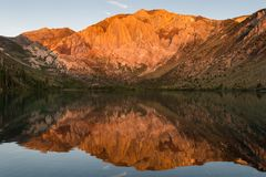 Sunrise casts golden light on mountain peaks reflected in the calm waters of alpine lake royalty free stock photos