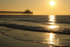 Sunrise Cherry Grove Pier Myrtle Beach Landscape. A beautiful sunrise over the famous landmark Cherry Grove ocean beach pier, reflecting off the water in Myrtle Royalty Free Stock Photos
