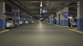 Cars on underground parking inside building stock video footage