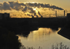 Sunrise in a city with pipes and smoke reflected in a pond Royalty Free Stock Photo