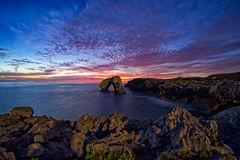 Sunrise on the cliff. Formation of islets and rocks due to the erosion of the sea on the cliffs Stock Photography