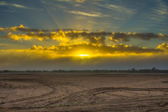 Sunrise through clouds above ploughed field Stock Photography