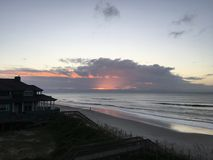 Sunrise over the Atlantic Ocean Coastline, North Carolina. Sunrise with clouds and ocean waves in front of a beachhouse off the Atlantic coast of Topsail Island Stock Image