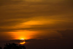 Sunrise on a cloudy morning. Orange sunrise as the sun peaks through the clouds Stock Photography