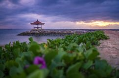 Sunrise in Cloudy Morning at Sanur Beach with Pavilion and Ornamental Plant. A View From Hotel Garden stock images