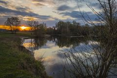 Sunrise with cloudy sky, the sun and the river Stock Photo
