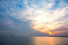 Sunrise in cloudy weather over the sea without waves royalty free stock photo