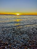 Sunrise on a coast full of rocks royalty free stock images