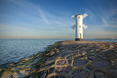 Sunrise on the coast, lighthouse windmill. Royalty Free Stock Photos