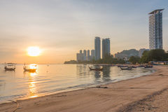 Sunrise at the coast of Tanjung Bungah, Penang, Malaysia. With few buildings and boats in the shot Stock Image