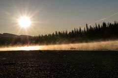 Sunrise after a cold night at Pelly River, Yukon. The warmer water than the air temperature after a cold night on Pelly River cauces the fog over the water. The stock images