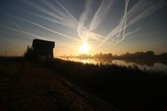 Sunrise with colored aircraft trails, fog on the meadows and at River Hollandsche IJssel. In the Netherlands at nieuwerkerk stock image