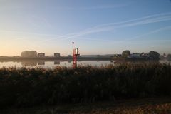 Sunrise with colored aircraft trails, fog on the meadows and at River Hollandsche IJssel. In the Netherlands at nieuwerkerk stock photography