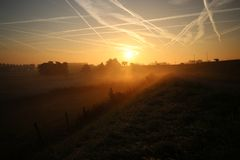 Sunrise with colored aircraft trails, fog on the meadows and at River Hollandsche IJssel. In the Netherlands at nieuwerkerk royalty free stock photos