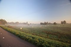 Sunrise with colored aircraft trails, fog on the meadows and at River Hollandsche IJssel. In the Netherlands at nieuwerkerk stock images