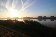 Sunrise with colored aircraft trails, fog on the meadows and at River Hollandsche IJssel. In the Netherlands at nieuwerkerk royalty free stock photo